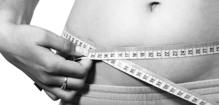 bauchfett beim intermittierendes fasten abbauen, Frau misst ihren Bauchumfang