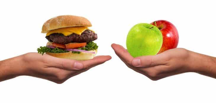 beim intervallfasten sind kleine suenden erlaubt: eine hand mit einem Burger und eine Hand mit einem Ampfel