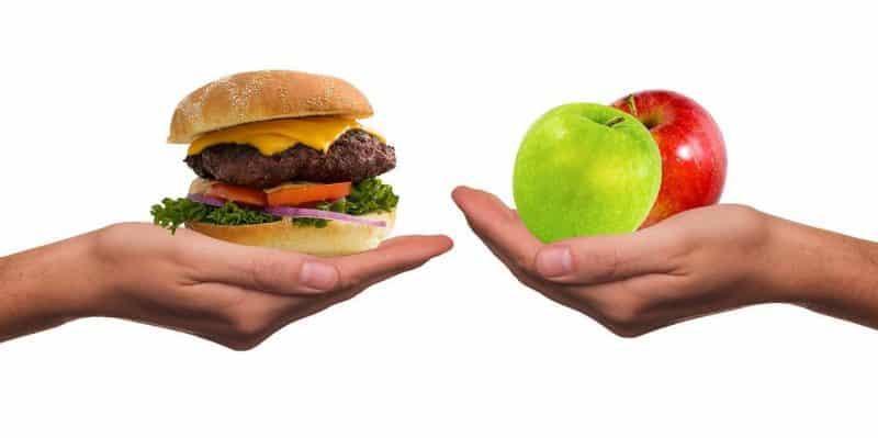 warum essen wir zu viel? beim intervallfasten sind kleine suenden erlaubt: eine hand mit einem Burger und eine Hand mit einem Ampfel