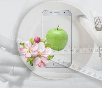 Bauch mit Maßband und Besteck und Apfel