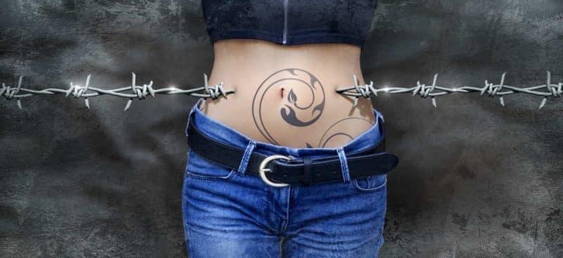 Hunger und Sättigung beim Intervallfasten - tätowierter Bauch einer Frau