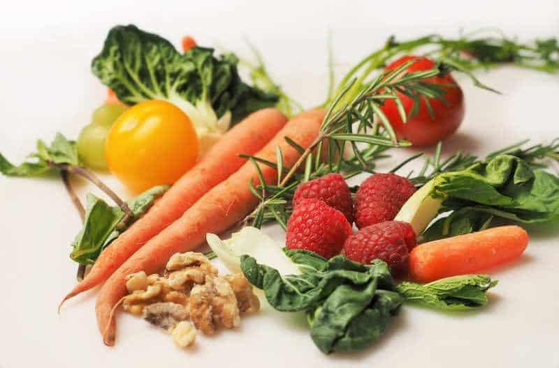 buntes Obst und Gemüse mit Möhren, Nüssen und Himbeeren