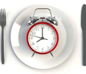 Ist intermittierendes Fasten gesund: Wecker auf Teller