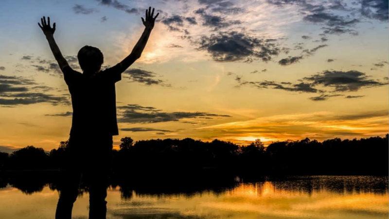 Erfahrung Intervallfasten - Mann steht am See bei Dämmerung