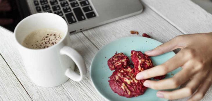 Hunger beim intermittierenden Fasten - Frau am Laptop beim Naschen