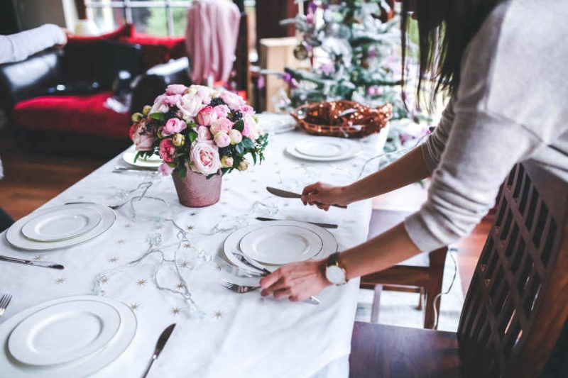 Intervallfasten an Feiertagen - Frau deckt Weihnachtstisch