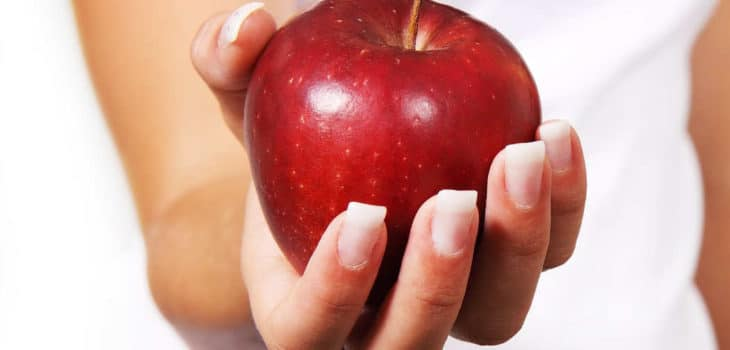 Intervallfasten im Test - Frau hält Apfel